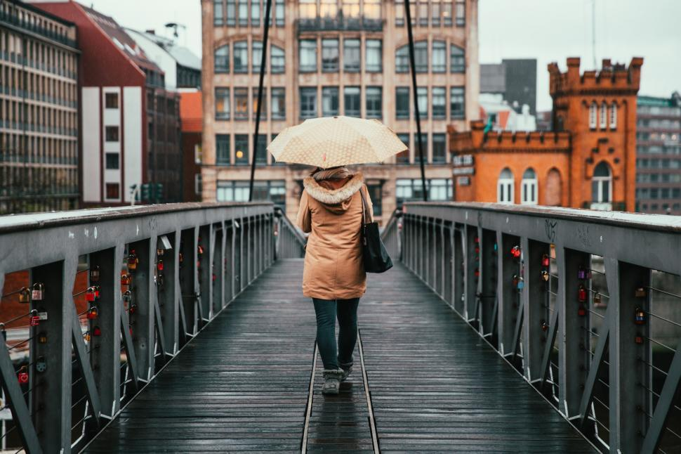 Download Free Stock HD Photo of A woman holding umbrella walking on the bridge Online