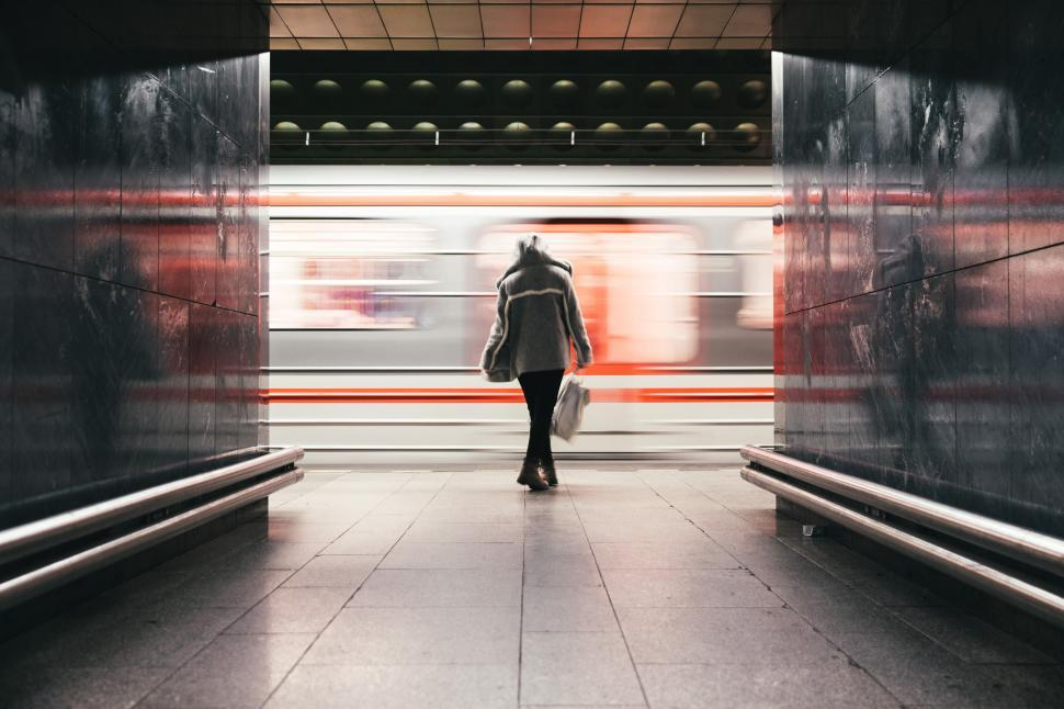 Download Free Stock HD Photo of A woman in hooded jacket waits for the train Online