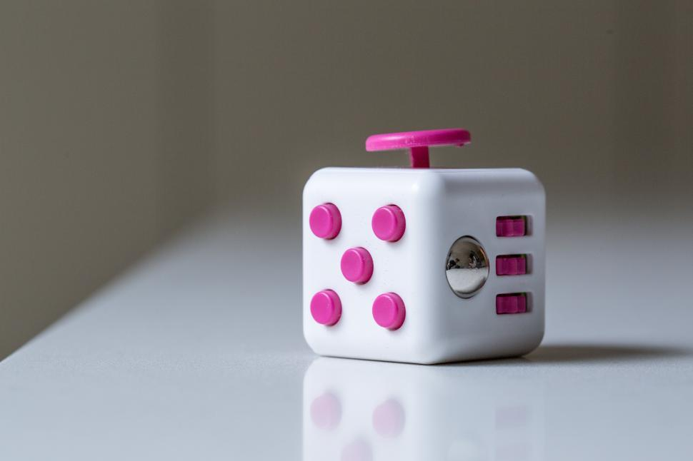 Download Free Stock HD Photo of Close up of pink and white fidget cube Online