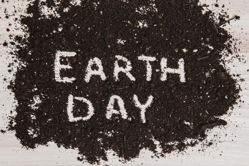 Download Free Stock HD Photo of The text  EARTH DAY  written out in dark soil on a white wooden surface Online