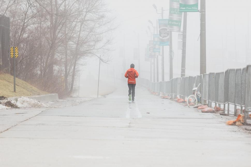 Download Free Stock HD Photo of Back view of a person jogging on a foggy day Online