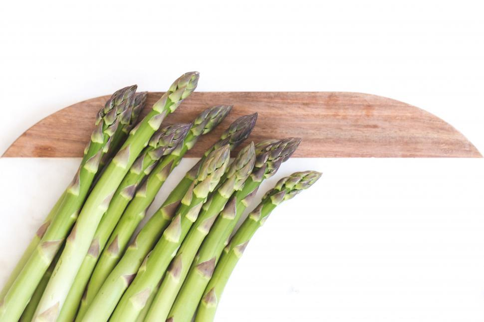 Download Free Stock HD Photo of A pile of fresh asparagus on cutting board Online