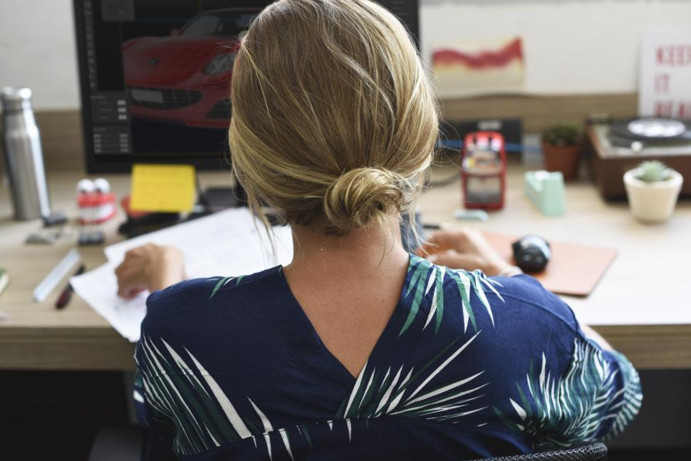 Download Free Stock HD Photo of Rear view of a blonde woman working at her desk Online