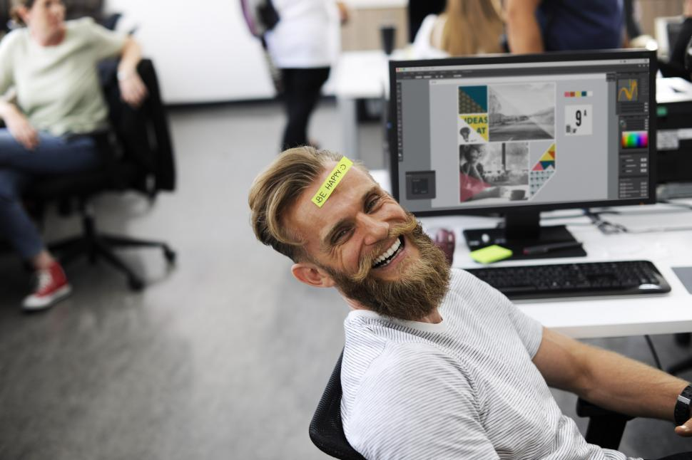Download Free Stock HD Photo of A happy employee lying in the chair with a sticky note on his fo Online