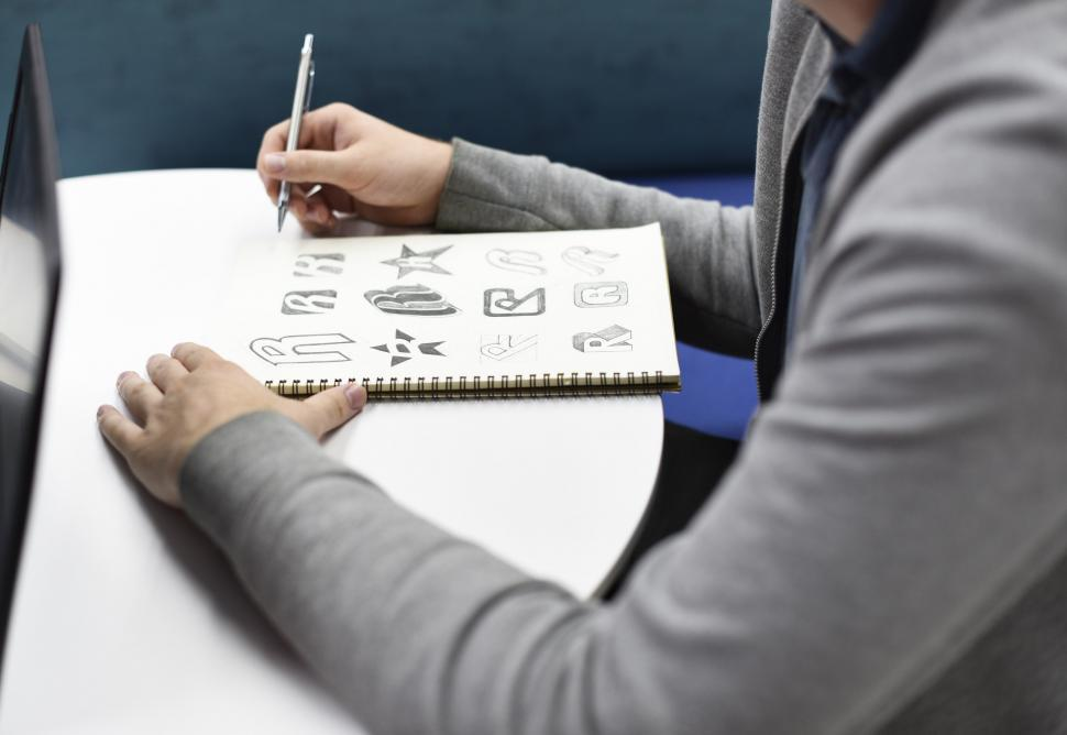Download Free Stock HD Photo of An artist s hands creating logos on the sketch book Online