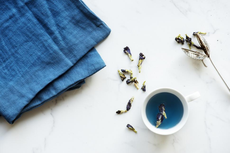 Download Free Stock HD Photo of Flat lay of a cup filled with butterfly-pea tea and a blue linen Online