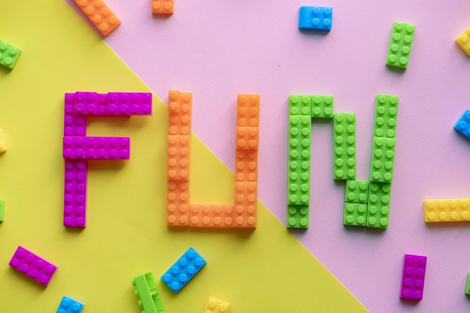 Download Free Stock HD Photo of Flat lay of the text FUN written with plastic toy bricks Online