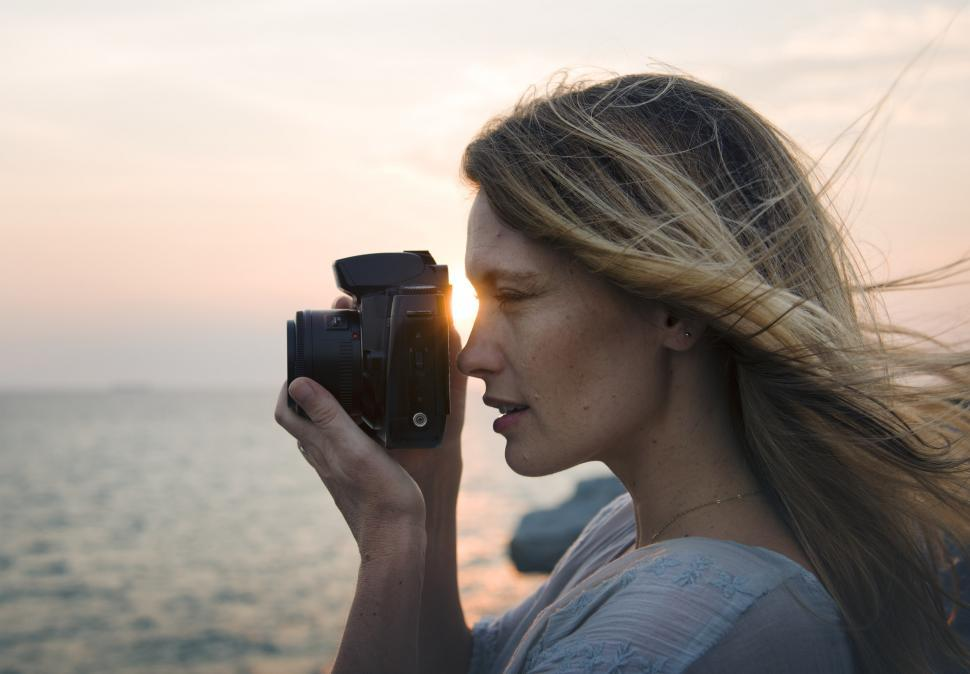 Download Free Stock HD Photo of A young caucasian woman taking photograph at a seashore Online