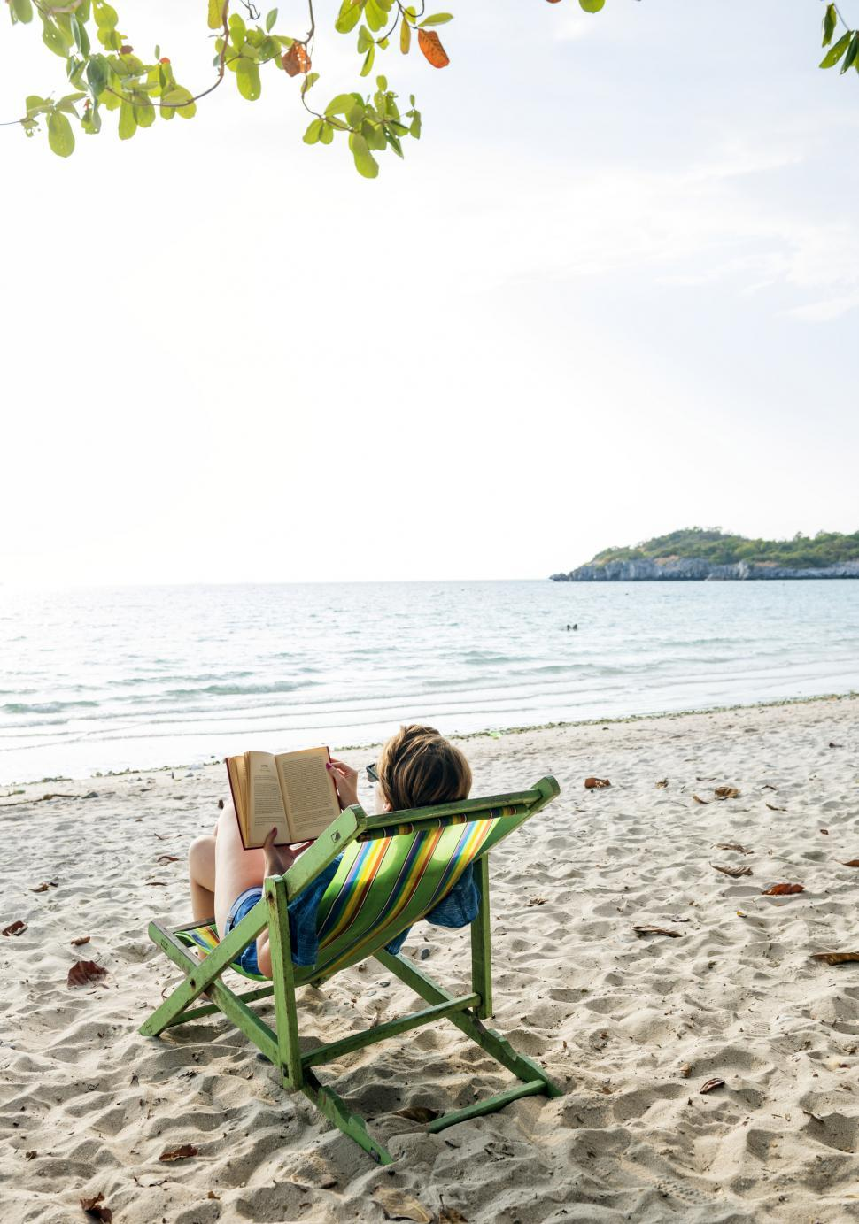 Download Free Stock HD Photo of A young woman reading book on the beach Online