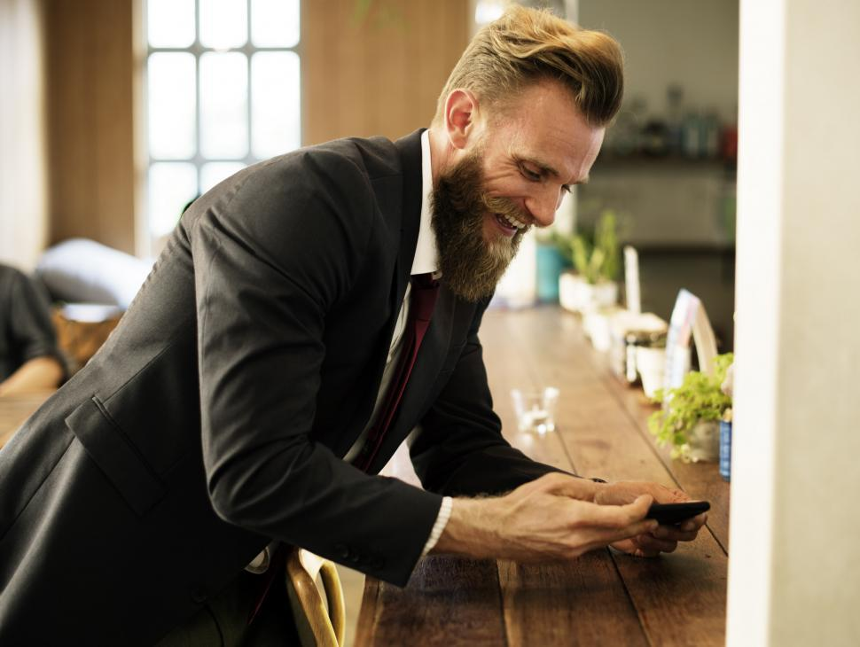 Download Free Stock HD Photo of A smiling bearded man looking at his mobile phone Online