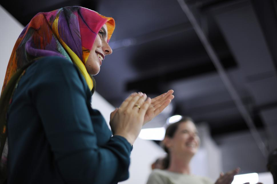 Download Free Stock HD Photo of A young woman wearing headscarf clapping Online