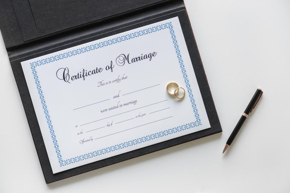 Download Free Stock HD Photo of A blank Certificate of Marriage with wedding rings and a pen Online