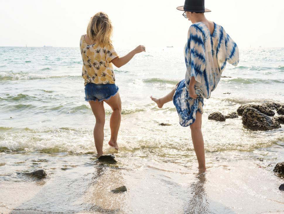 Download Free Stock HD Photo of Rear view of two women splashing seawater with their l Online