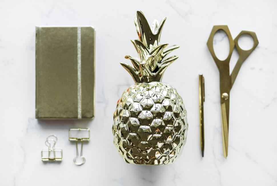 Download Free Stock HD Photo of Flat lay of a golden pineapple shaped paper weight with others s Online