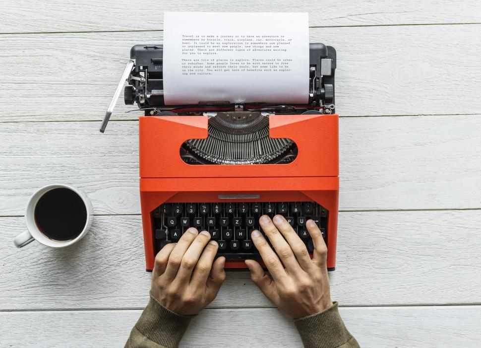 Download Free Stock HD Photo of Flay lay of hands typing on red typewriter Online