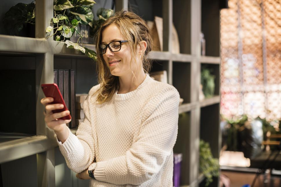 Download Free Stock HD Photo of Close up of a young Caucasian woman looking at her mobile phone Online