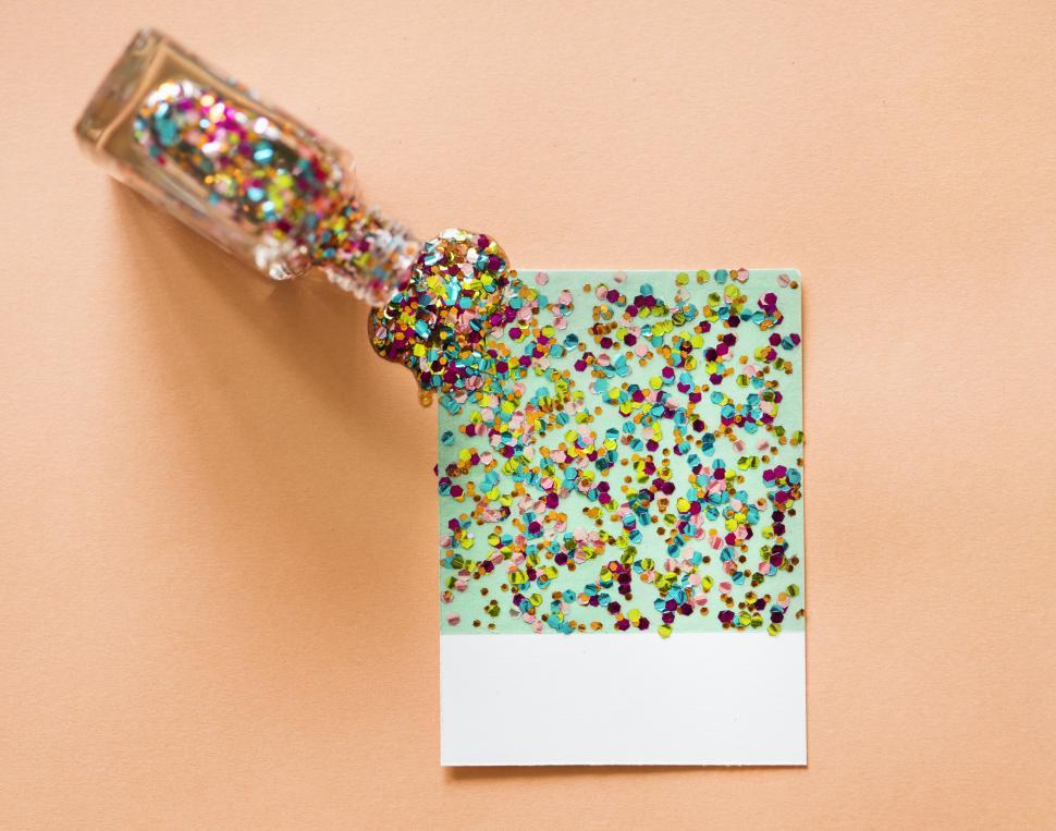 Download Free Stock HD Photo of Colorful hexagon shaped glitter sparkles poured from a bottle Online