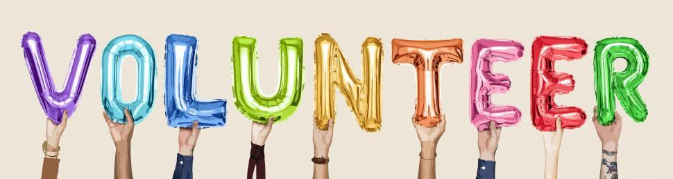 Download Free Stock HD Photo of Word  VOLUNTEER  formed by holding inflated alphabet shaped balloons with hands Online