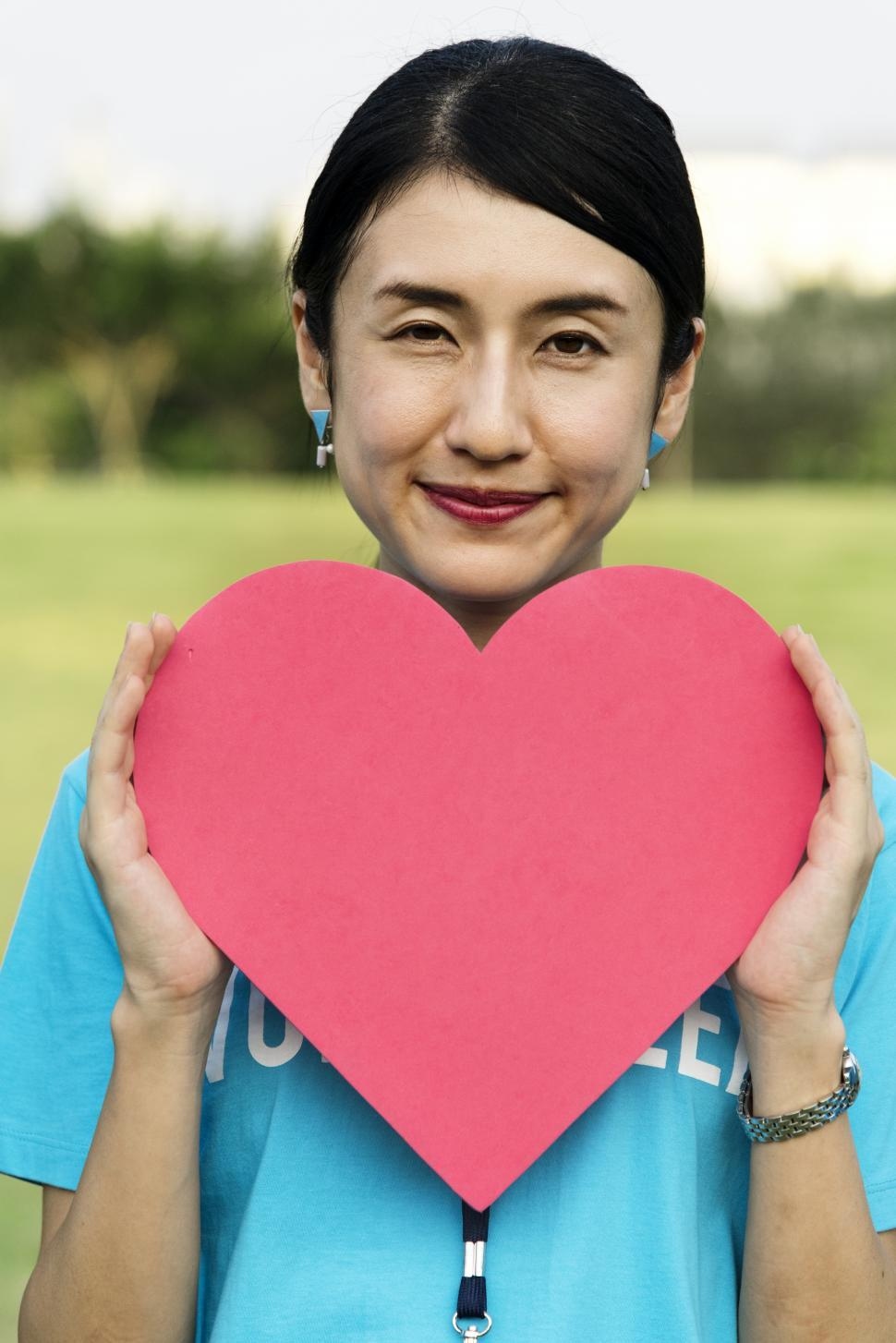 Download Free Stock HD Photo of A young Asian ethnicity woman posing with a red heart shaped cut out Online