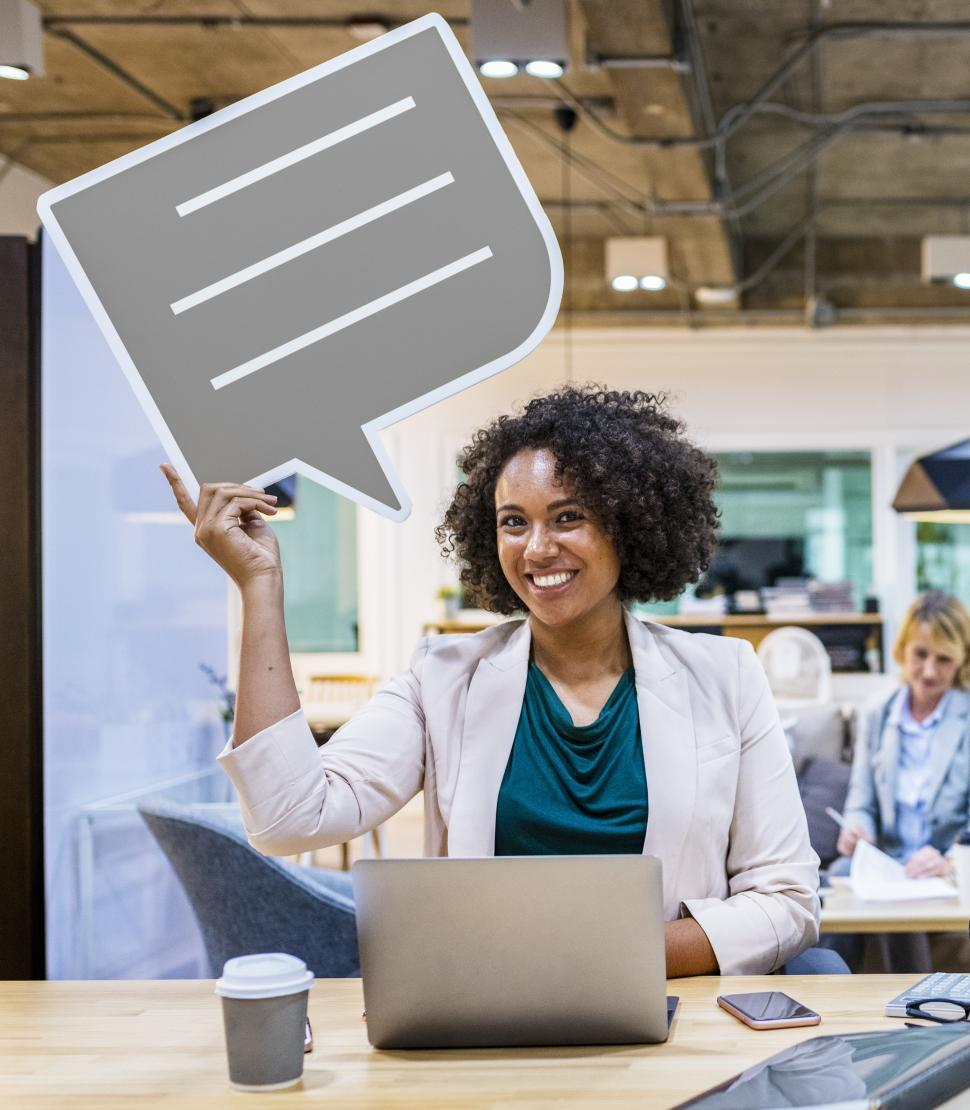 Download Free Stock HD Photo of A young African ethnicity woman with curly hair holds a speech bubble cardboard cutout Online