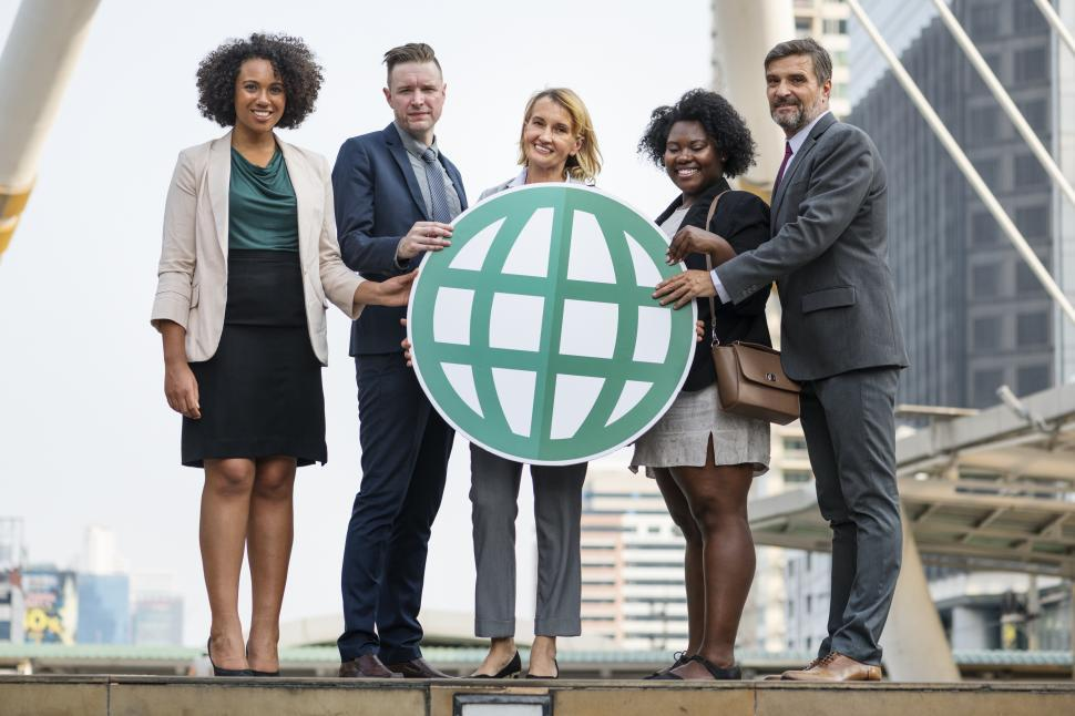 Download Free Stock HD Photo of Colleagues posing with a globe symbol cardboard cutout Online