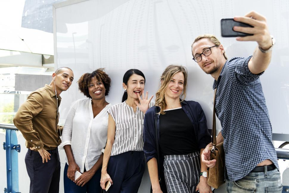 Download Free Stock HD Photo of Multiethnicity people taking a group photo with mobile phone Online
