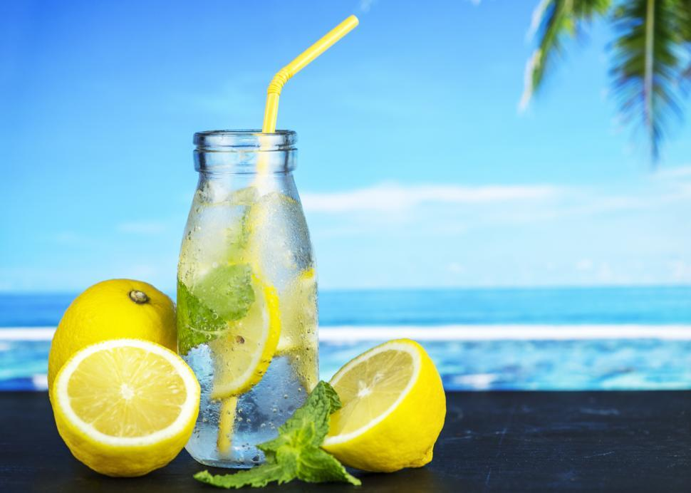 Download Free Stock HD Photo of Close up of chilled lemonade in a bottle with yellow straw Online