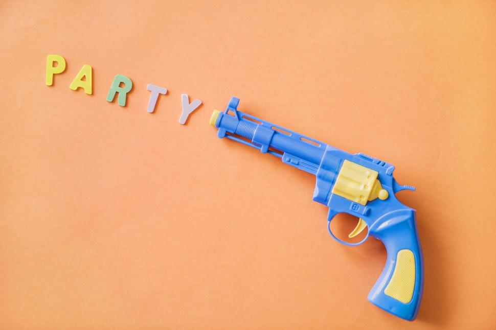 Download Free Stock HD Photo of Flat lay of the word PARTY depicted as being fired from a toy gun Online