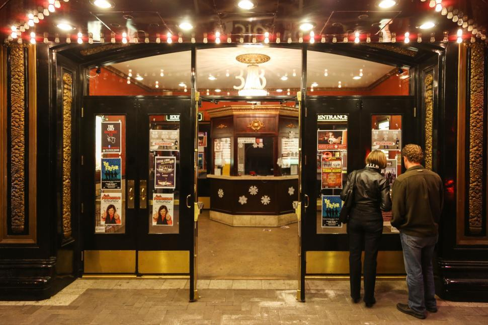 Download Free Stock HD Photo of Couple at entrance to a theater Online