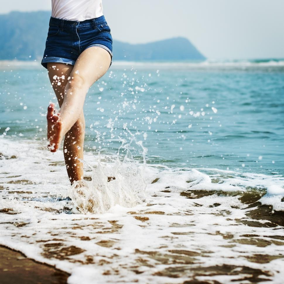 Download Free Stock HD Photo of A young woman s legs splashing water on the beach Online