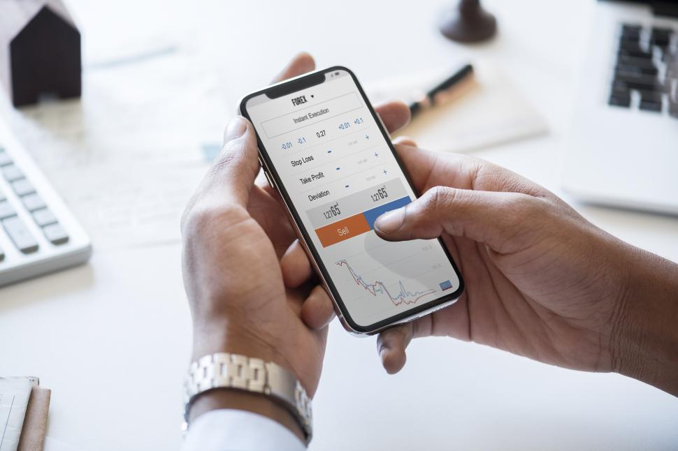Download Free Stock HD Photo of Hands holding a mobile phone showing profit and loss data Online