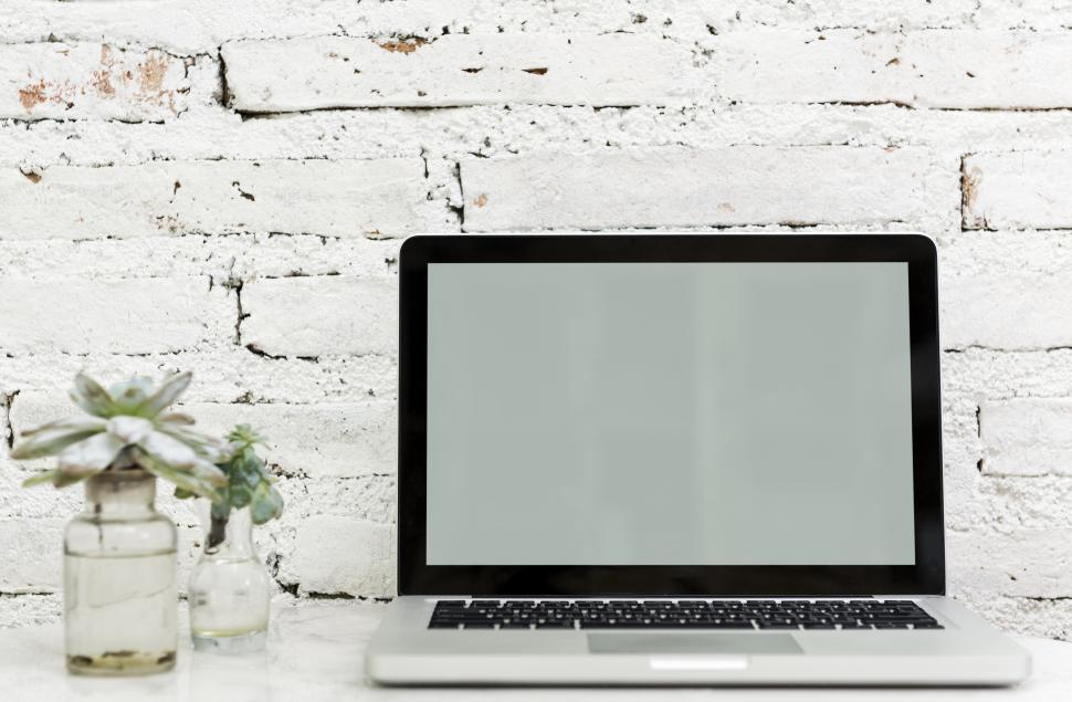 Download Free Stock HD Photo of A laptop along with glass flower pots the table Online