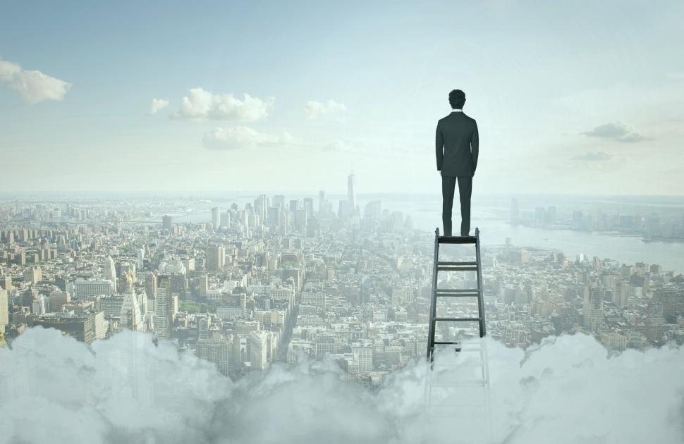 Download Free Stock HD Photo of Businessman On Top of Ladder Overlooking Manhattan Online