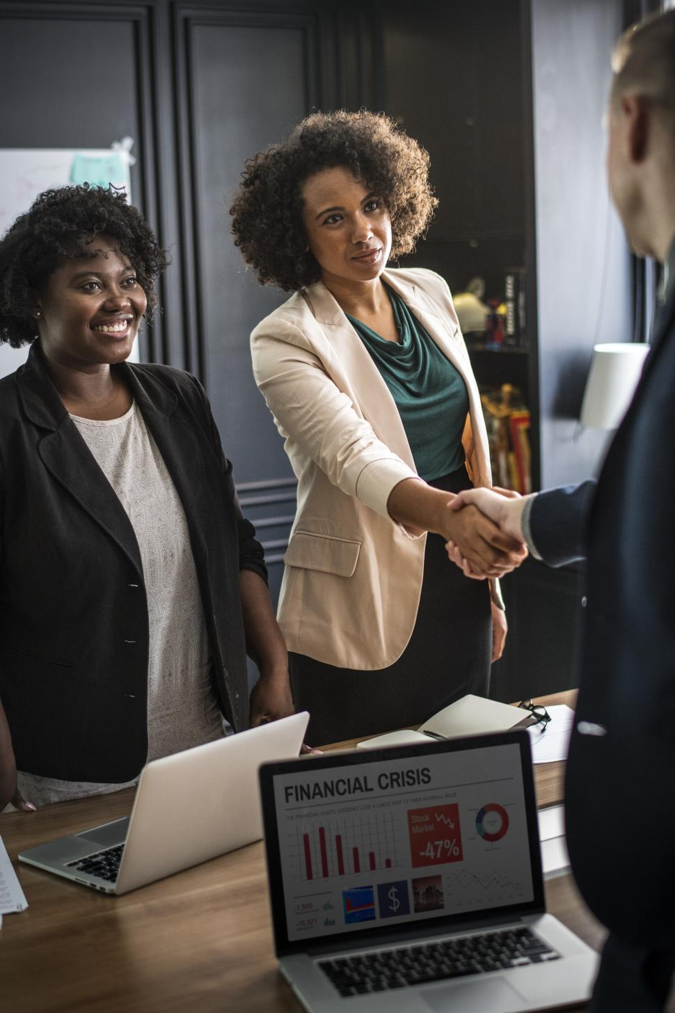 Download Free Stock HD Photo of Three colleagues in the office shake hands Online