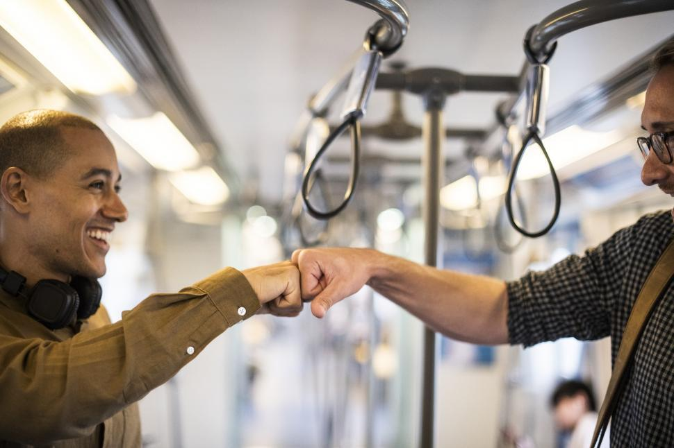 Download Free Stock HD Photo of Commuters giving Fist Bump on the Train Online