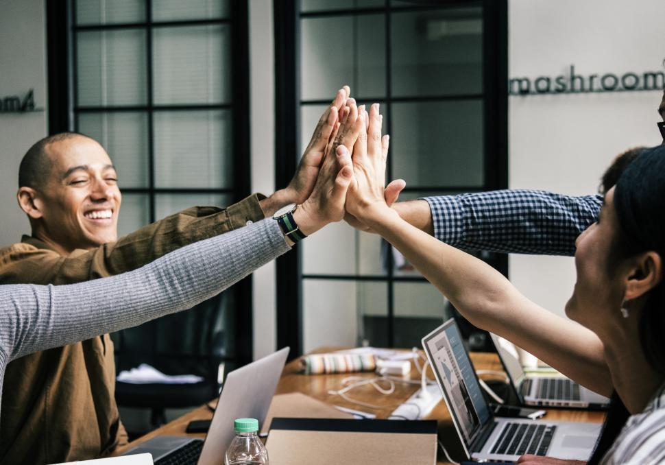 Download Free Stock HD Photo of Coworkers giving high five in the office Online