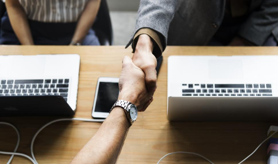 Download Free Stock HD Photo of Handshake between two business people over workstation Online