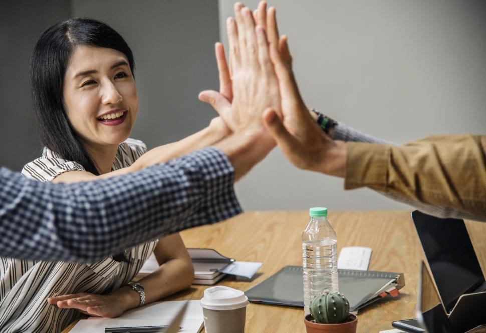 Download Free Stock HD Photo of Coworkers giving high five over table in the office Online