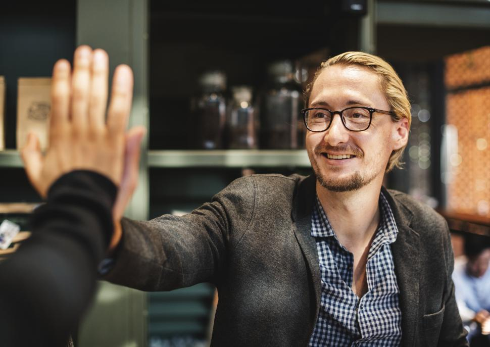 Download Free Stock HD Photo of Happily giving high five in the office Online