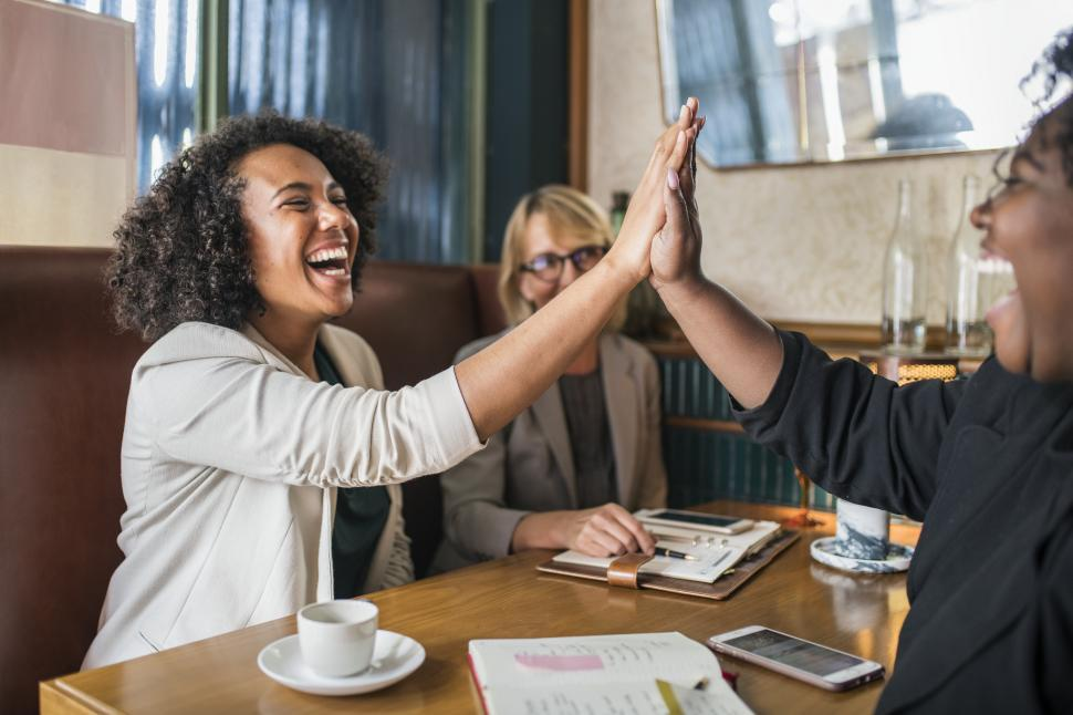 Download Free Stock HD Photo of Laughing people giving high five in the cafe Online