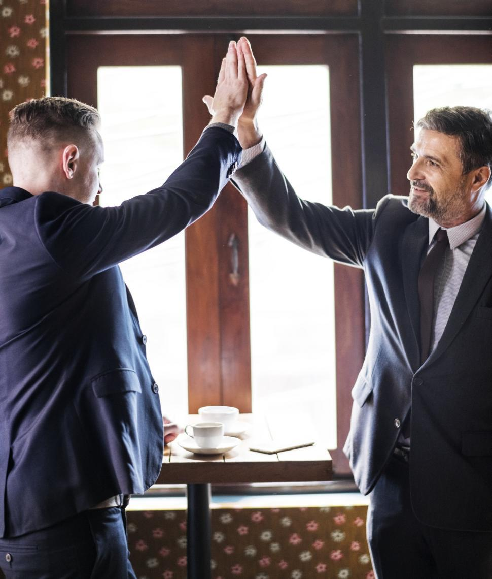 Download Free Stock HD Photo of Smiling colleagues in suits giving high-five Online