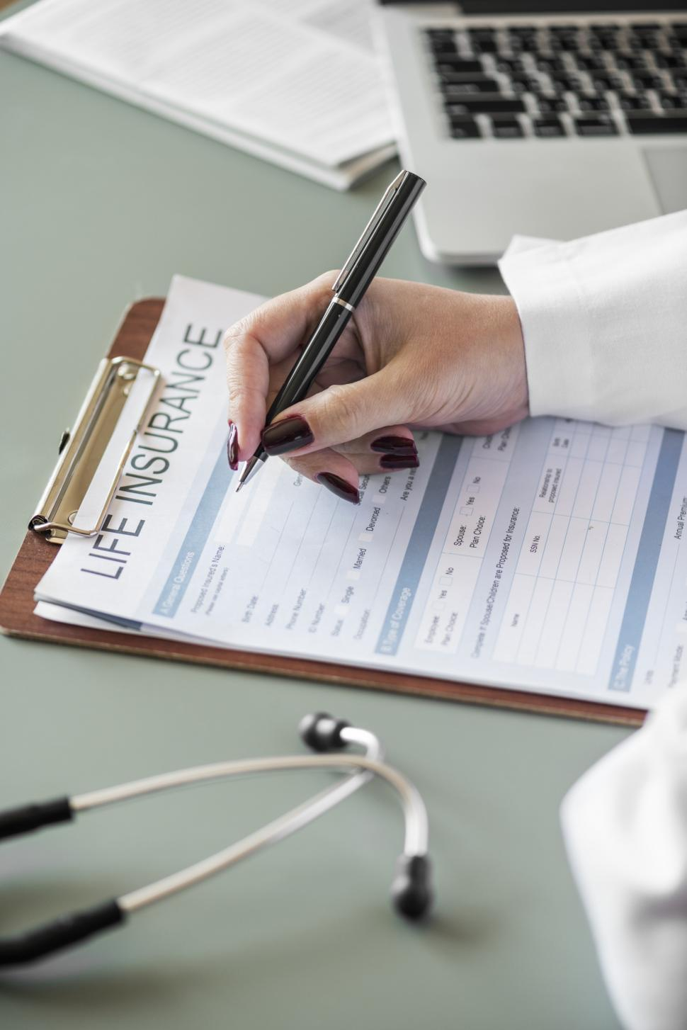 Download Free Stock HD Photo of Close up of a doctor s hand writing on the insurance questionnaire Online