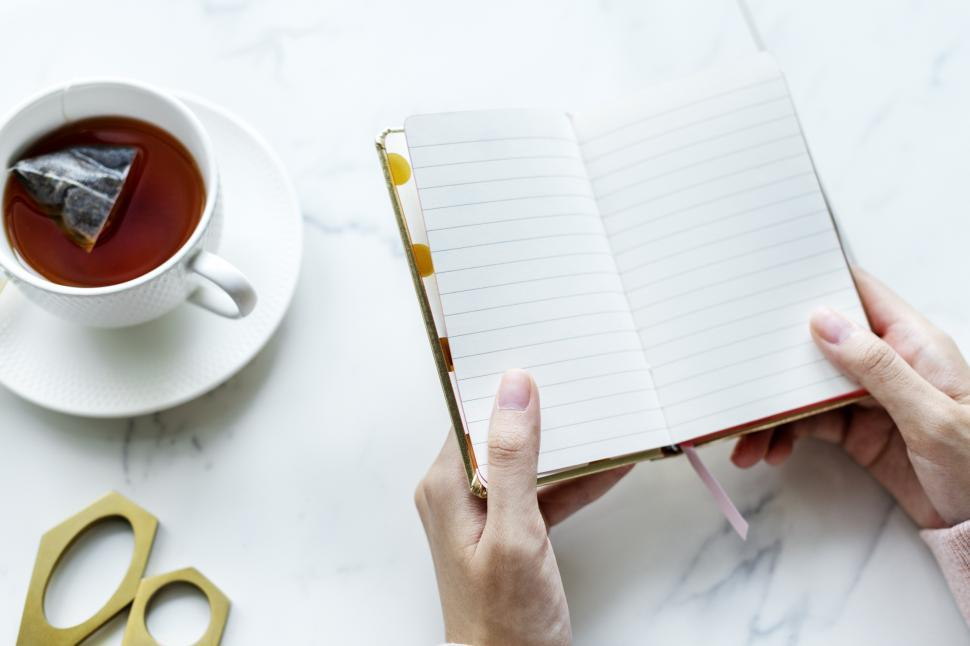 Download Free Stock HD Photo of Overhead view of a person s hands holding a notebook surrounded with a cup of tea and scissors on the marble surface Online