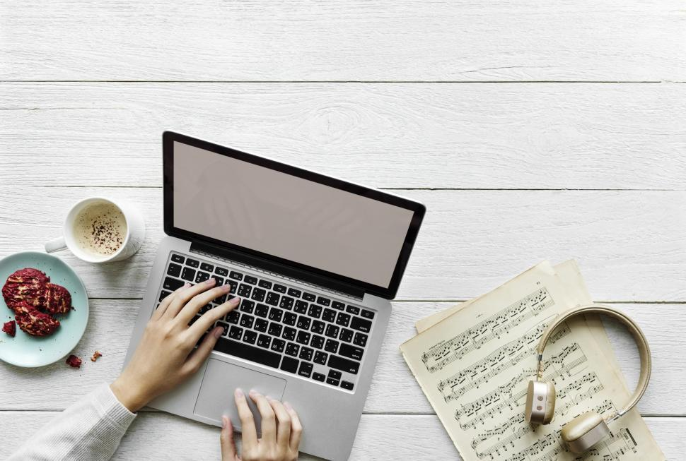 Download Free Stock HD Photo of Close up of a person s hands typing on laptop alongside music notes and a headphone Online