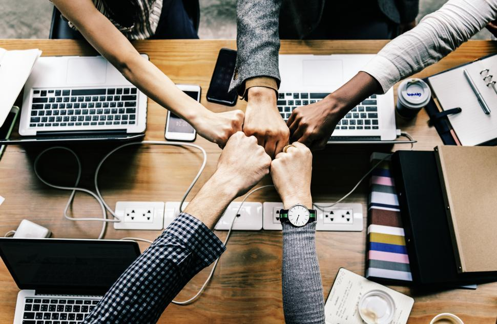 Download Free Stock HD Photo of A business team giving Fist Bump in agreement across laptops Online
