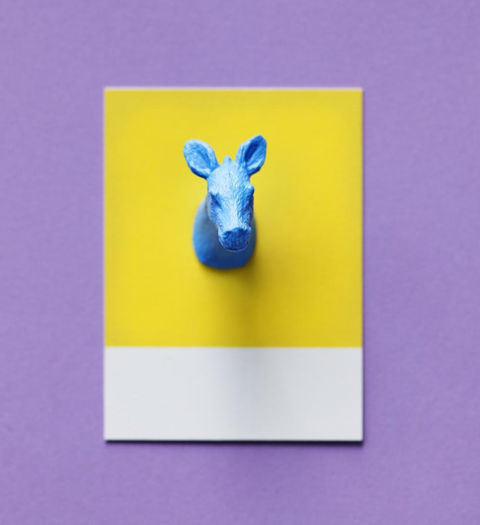 Download Free Stock HD Photo of Flay lay of a miniature toy donkey s head on a spaced cardboard frame Online