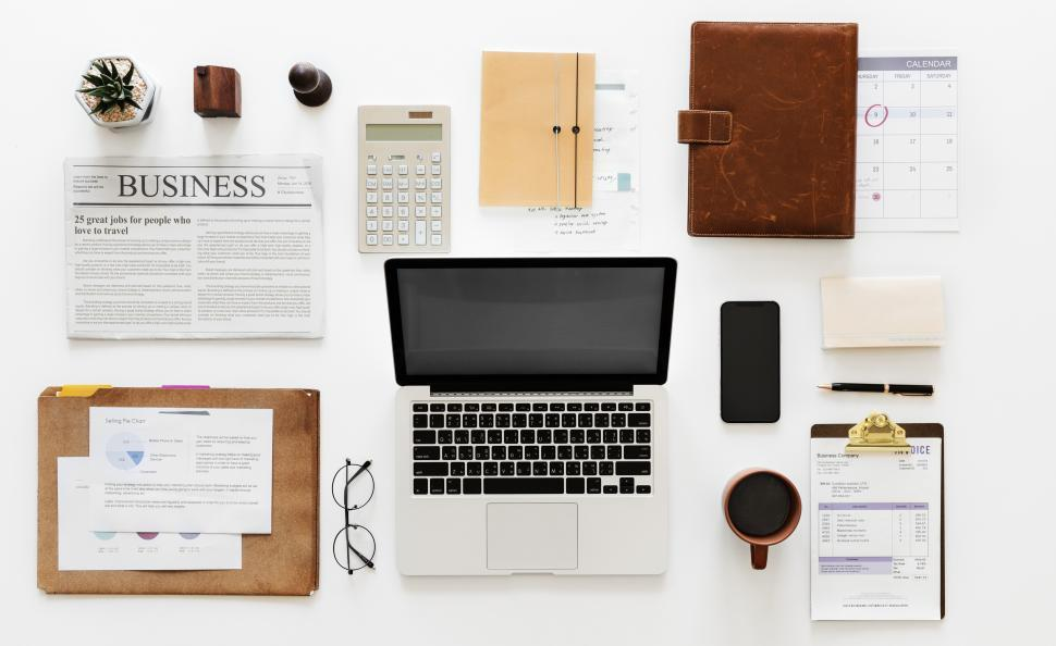 Download Free Stock HD Photo of Laptop and a coffee mug along with other items in workspace area Online