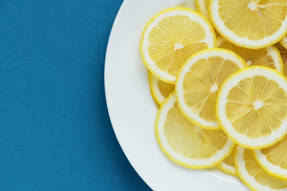 Download Free Stock HD Photo of Flat lay of lemon slices on white plate, blueish background Online