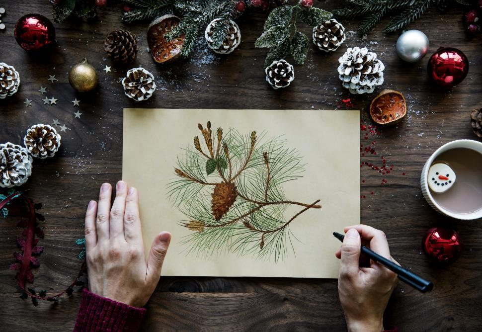 Download Free Stock HD Photo of Over the dead view of hands holding a pine cone sketch Online
