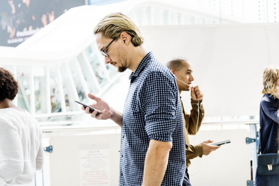 Download Free Stock HD Photo of A bearded Caucasian man looks at his mobile phone Online